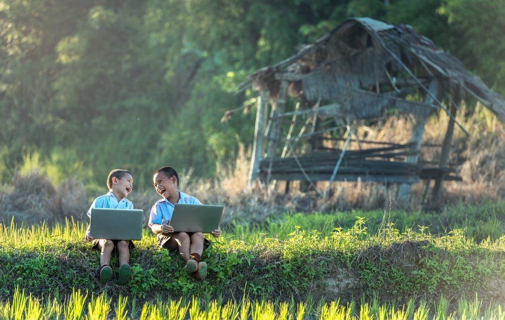 Kids Using Laptop On Field