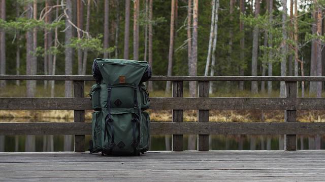 green backpack on bridge