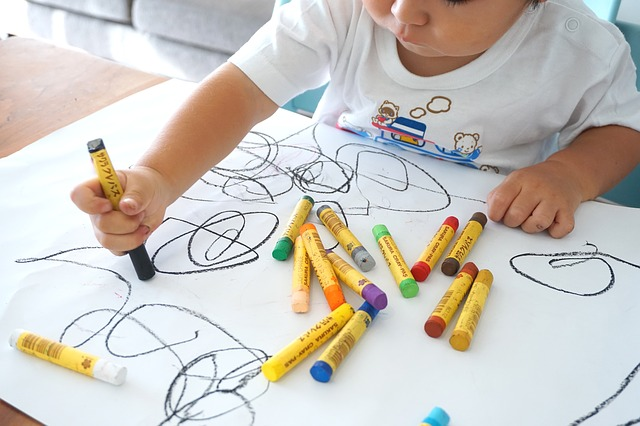 Toddler doodling with crayons
